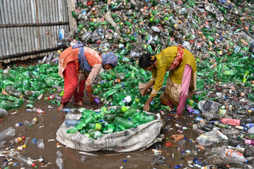 Kinder stehen in einem Müllberg und sammeln Flaschen