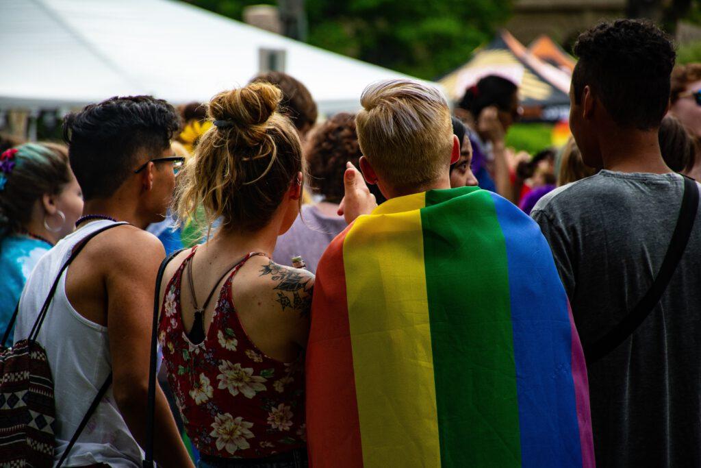 Menschen stehen eng beieinander und haben eine Regenbogenfalgge bei sich